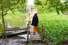 Een Giang, Vietnam - 29 Nov., 2014: Het meisje die van Chamcampa op houten brug lopen die Cham-dorp verbinden met buitenkant De C Stock Afbeeldingen
