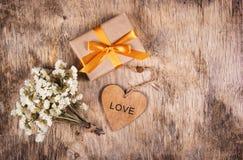Een giftdoos met een gouden boog, witte bloemen en een houten hart Een klein heden met een gouden lint op een houten achtergrond Stock Foto's