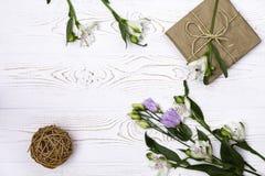 Een giftvakje in kraftpapier-document en bloemen wordt verpakt en streng op een witte lijstbovenkant die Vlak leg Exemplaarruimte royalty-vrije stock foto