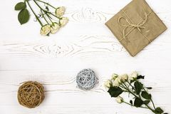 Een giftvakje in kraftpapier-document, streng, beige kleine bloemen van rozen en rotanballen wordt verpakt op een wit tafelblad d royalty-vrije stock foto