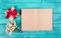 Een giftvakje met een satijnlint en een open boek met blanco pagina's op een blauwe achtergrond Achtergronden en texturen De ruim Stock Afbeelding