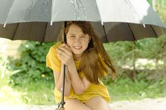 Een girl under the big umbrella in a downpour Stock Photography