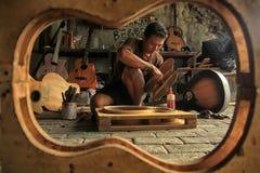 Een gitaarvakman is bezig het maken van orden van zijn cliënten stock afbeeldingen