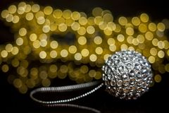 Een glanzende zilveren bal van een Kerstboom die op een lijst aangaande de achtergrond van gerlyani met mooie bokeh liggen stock fotografie