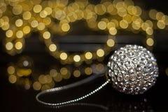 Een glanzende zilveren bal van een Kerstboom die op een lijst aangaande de achtergrond van gerlyani met mooie bokeh liggen stock afbeeldingen