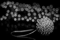 Een glanzende zilveren bal van een Kerstboom die op een lijst aangaande de achtergrond van gerlyani met mooie bokeh liggen Rebecc stock foto's