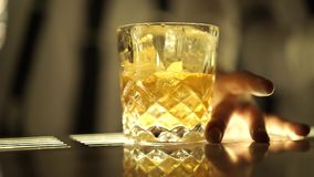 Een glas alcoholische drank en ijsblokjes stock videobeelden