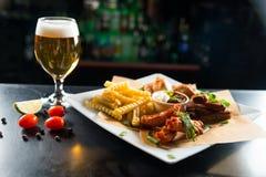 Een glas bier en een snack op een witte plaat, gebraden gerechten en ribben stock afbeelding