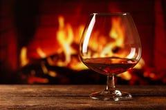 Een glas cognac op houten lijst met vuurachtergrond stock afbeeldingen