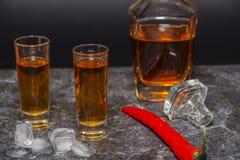 Een glas cognac of whisky met Spaanse peper royalty-vrije stock afbeeldingen
