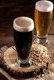 Een glas donker en licht bier op een houten tribune met gerstkorrels op een bruine lijst stock fotografie