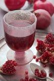 Een glas granaatappelsap met verse granaatappelvruchten en zaden op rustieke achtergrond stock afbeeldingen