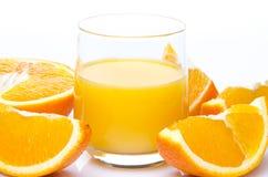 Een glas jus d'orange met oranje kwarten Stock Foto's