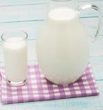 Een glas melk en een melkkruik op plaidtafelkleed Royalty-vrije Stock Fotografie