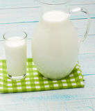 Een glas melk en een melkkruik op plaidtafelkleed Stock Fotografie