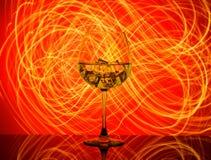 Een glas met een drank en ijsblokjes op een rode achtergrond Royalty-vrije Stock Afbeelding