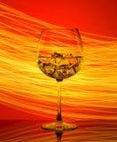 Een glas met een drank en ijsblokjes op een rode achtergrond Stock Foto