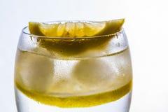 Een glas met water, ijs en citroen stock afbeeldingen
