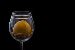 Een glas op een zwarte achtergrond, pinda en citroen, de contour van het glas met citroen en pinda's het thema van gezond Stock Foto