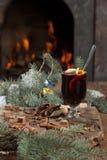 Een glas overwogen wijn en kruiden op een achtergrond van een brandende open haard Stock Foto's