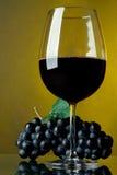 Een glas rode wijn en druiven Stock Foto