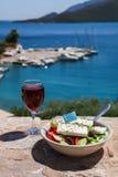 Een glas rode wijn en kom Griekse salade met Griekse vlag door de overzeese mening, concept van de de zomer het Griekse vakantie Royalty-vrije Stock Foto