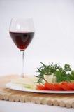 Een glas rode wijn met kaas, kruiden en tomaat Royalty-vrije Stock Foto