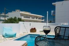 Een glas rode wijn op de lijst door de pool royalty-vrije stock afbeelding