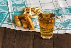 Een glas thee, koekjes en ongezuurde broodjes op een houten lijst Royalty-vrije Stock Afbeelding