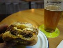 Een glas van bier en een hamburger Mooi en heerlijk voedsel, schuimend bier in een glas details stock fotografie