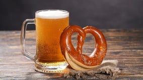Een glas van bier en pretzel op een houten lijst stock footage