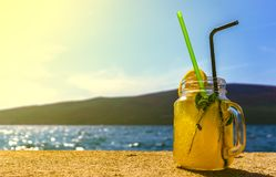 een glas van cocktail op de achtergrond van het overzees in goed weer royalty-vrije stock afbeelding