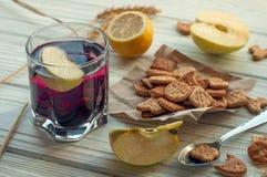 Een glas van een fruitdrank (sap), creckers, verse appelen en een citroen Stock Fotografie