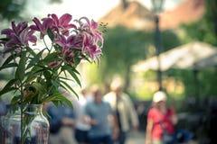 Een glas van lelies in een restaurant in het midden van de straat In de achtergrond vage mensen royalty-vrije stock fotografie