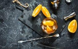 Een glas van Negroni-cocktail met sinaasappel en citroen Alcoholische drank met rum en vermouth op donkere steenlijst Royalty-vrije Stock Foto