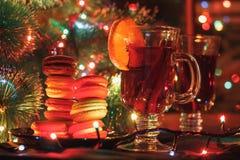 Een glas van overwogen wijn met kaneel en sinaasappel in Kerstmislichten Stock Fotografie