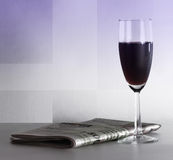 Een glas van rode wijn en een krant Royalty-vrije Stock Fotografie