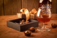 Een glas van sterke alcoholisch drinkt brandewijn of brandewijn en een doos chocolade op een donkere achtergrond royalty-vrije stock foto