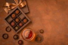 Een glas van sterke alcoholisch drinkt brandewijn of brandewijn en een doos chocolade op een donkere achtergrond Vlakke lay-out stock foto's