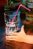 Een glas van water en een hand van kinderen Royalty-vrije Stock Afbeelding