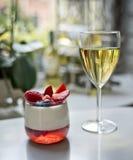 Een glas van witte wijn en een panakotadessert stock afbeelding