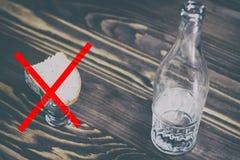 een glas van zuivere alcohol, een fles en een stuk van brood en kaas op een houten achtergrond een glas en op het een rood kruis  royalty-vrije stock foto