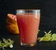 Een glas vers gedrukte grapefruit juice met het close-up van grapefruitplakken op een zwarte achtergrond stock afbeelding