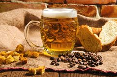 Een glas vers koud licht bier met brood op jute stock foto