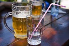 Een glas water en een mok bier Royalty-vrije Stock Foto's