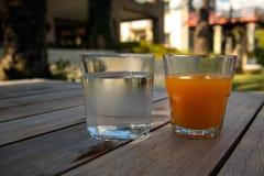 Een glas water en een glas jus d'orange op oud houten Ta stock foto