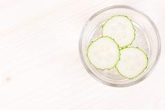 Een glas water met drie plakken van verse komkommer op een licht Stock Afbeelding