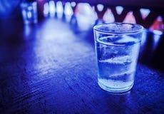 Een glas water met ijs, op de houten lijst Stock Afbeeldingen