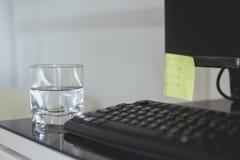 Een glas water zette op een werkende lijst stock fotografie