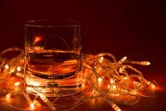 Een glas whisky en op de achtergrond een gloeiende slinger op een rode achtergrond met een exemplaar van ruimte stock foto